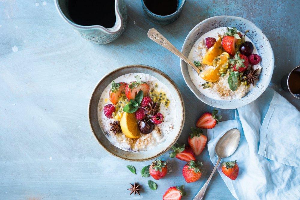 Selbstfürsorge Tipps - zwei Schalen mit Porridge, frischen Früchten
