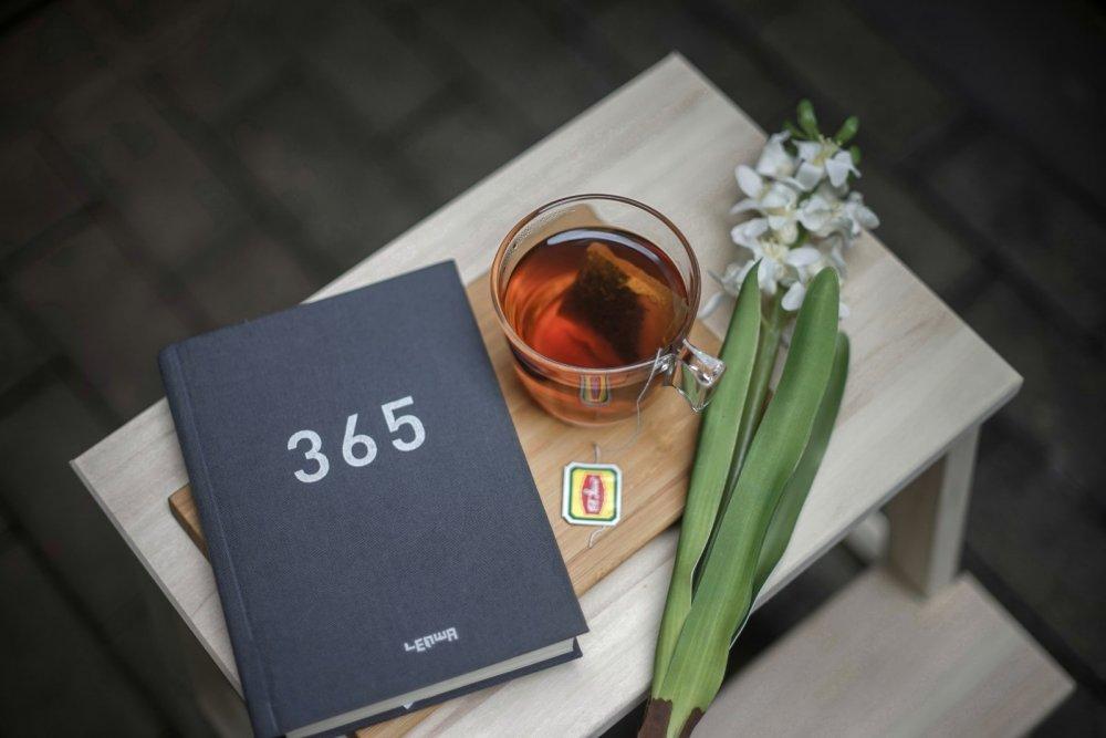 Selbstfürsorge Tipp: Sich Zeit für sich selbst nehmen - Ein Bild eines Tagebuchs, einer Blume und einer Tasse Tee