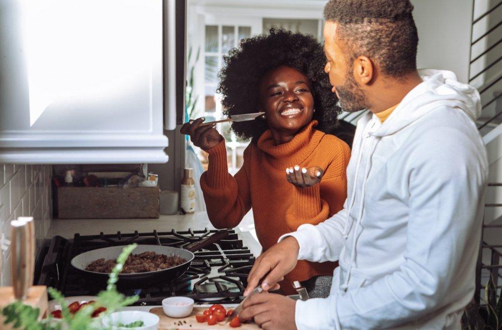 Selbstfürsorge Tipps: Probier mal was Neues - Bild zeigt ein junges Paar lachend beim Kochen am Herd.