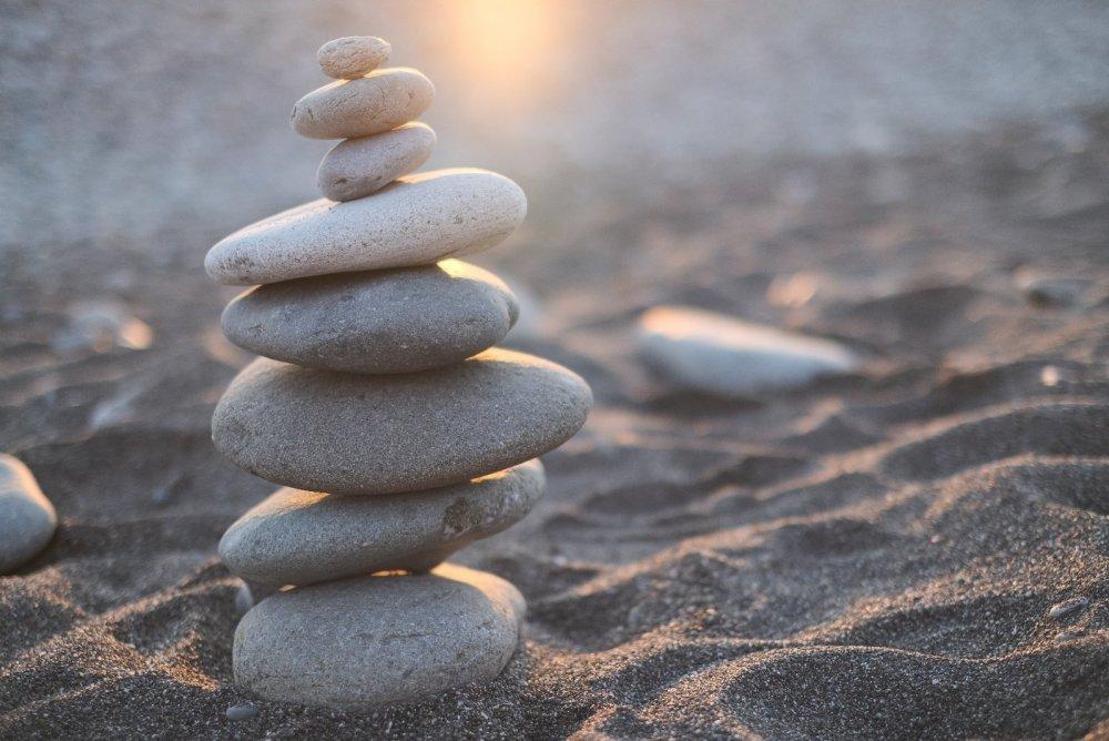 Inneren Frieden finden durch Gelassenheit und Balance - Das Bild zeigt aufeinander gestapelte Steine