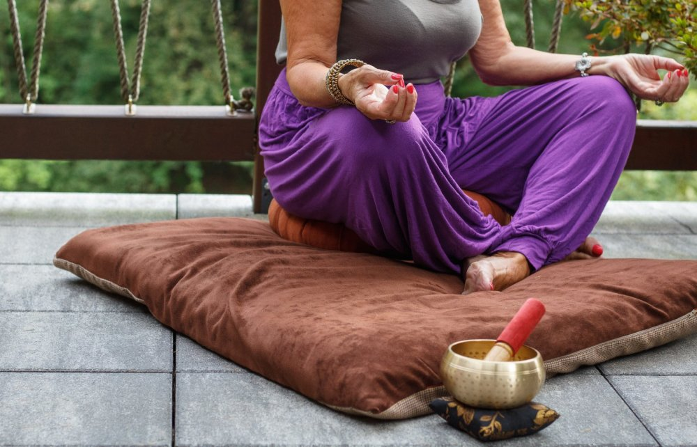 Inneren Frieden finden durch Achtsamkeit - das Bild zeigt eine ältere Frau im Lotussitz, nur die verschränkten Beine und die Arme sind zu sehen